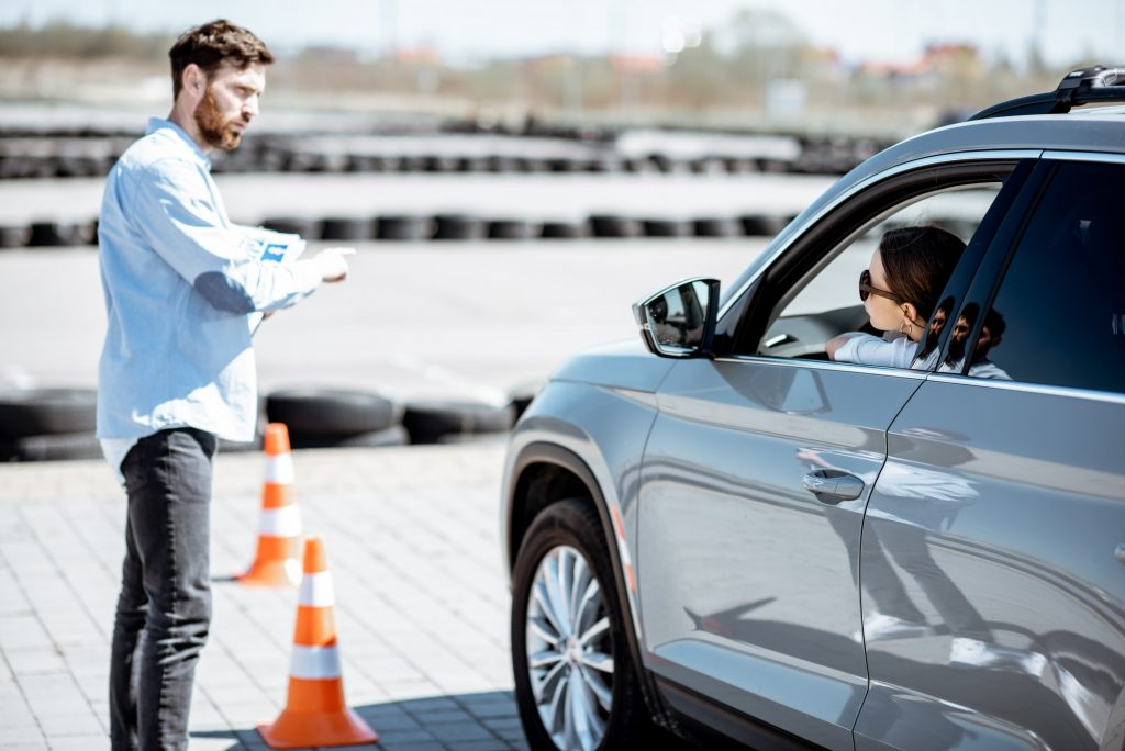 Instructor teaching to drive a car on the training ground