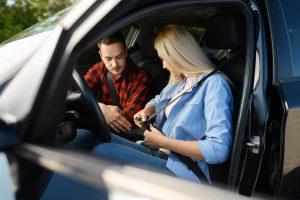 Student fastens seat belt in car, driving school