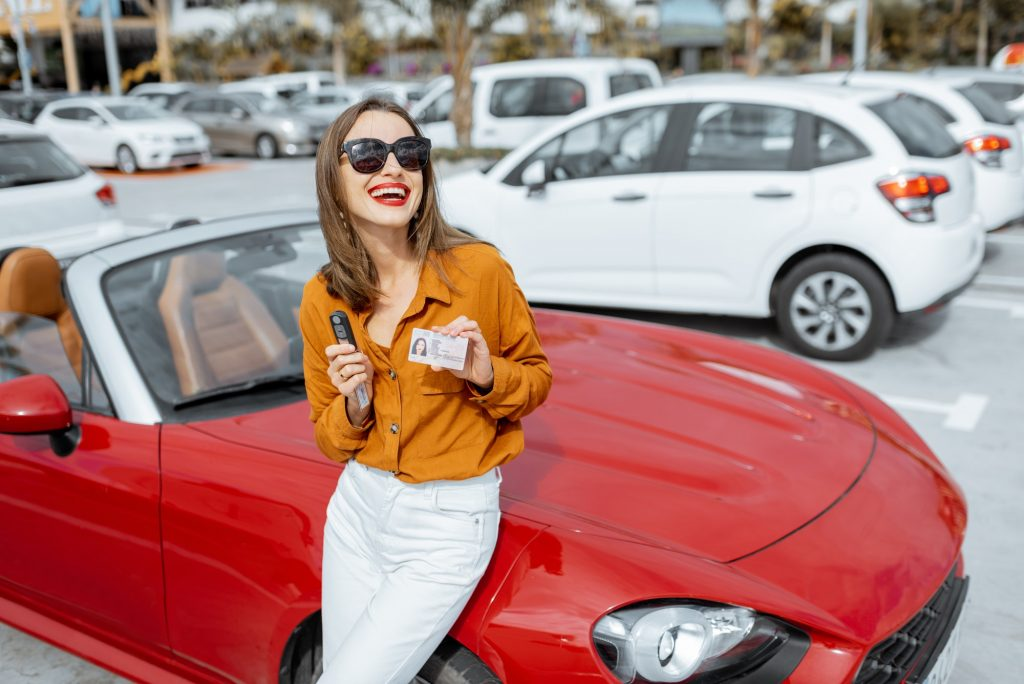 Woman with keys and license near the car at the parking